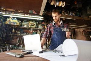 Mann mit Computer und Papierplänen auf der Werkbank