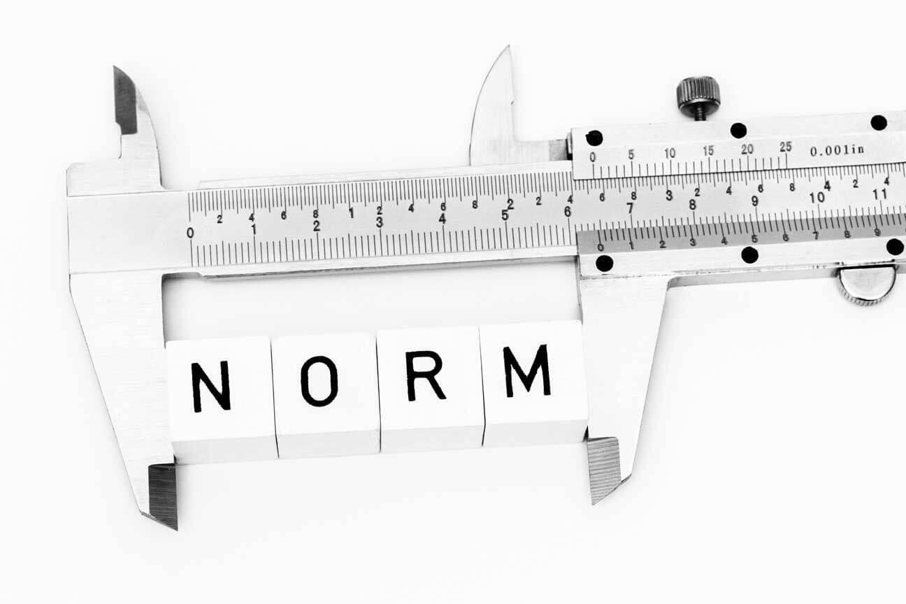 Ein Messschieber misst vier Würfel mit Buchstaben die zusammen das Wort Norm bilden